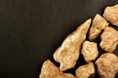 Золотые самородки на черной коже предпосылки. Крупный план. Стоковое Фото
