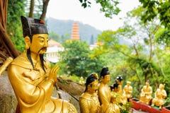 Золотые статуи Будды на предпосылке красных пагоды и леса i Стоковое Фото