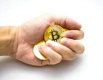 Золотые bitcoins в руке Символ цифров новой виртуальной валюты на белой предпосылке Стоковые Изображения