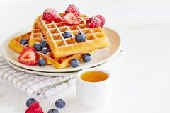 Золотые waffles с ягодами и чашкой меда Стоковые Фото