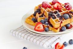 Золотые waffles с ягодами на белой таблице Стоковая Фотография RF