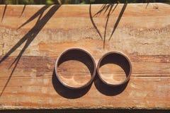 2 золотых обручального кольца кладя на деревянное Стоковая Фотография RF
