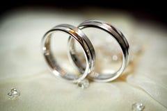 2 золотых обручального кольца на бежевой сатинировке лестницы портрета платья принципиальной схемы невесты wedding Стоковое Изображение RF