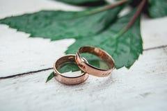 2 золотых обручального кольца на белом деревянном столе Стоковая Фотография RF