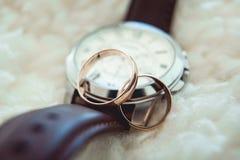 2 золотых обручального кольца на вахте с коричневым ремнем Стоковые Фото