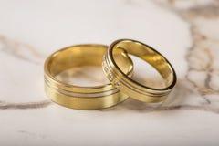 2 золотых обручального кольца на таблице Стоковые Изображения