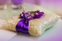 2 золотых обручального кольца на фиолетовой и белой малой подушке Стоковые Изображения
