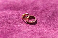 2 золотых обручального кольца на фиолетовой парче Стоковые Изображения RF