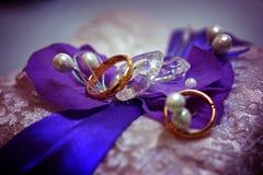 2 золотых обручального кольца на фиолетовой предпосылке с камнями, шнурке Стоковая Фотография