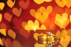 2 золотых обручального кольца с bokeh сердца на предпосылке Концепция Стоковое Фото