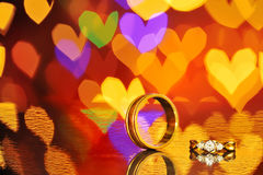 2 золотых обручального кольца с bokeh сердца на предпосылке Концепция Стоковые Фото