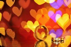 2 золотых обручального кольца с bokeh сердца на предпосылке Концепция Стоковые Изображения
