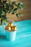 3 золотых пасхального яйца на голубой предпосылке Стоковое фото RF