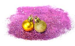 2 золотых шарика рождества на фиолетовом ярком блеске на белой предпосылке Стоковые Фотографии RF