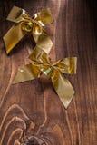 2 золотых boaws рождества с малыми колоколами на старое коричневое деревянном Стоковое Фото