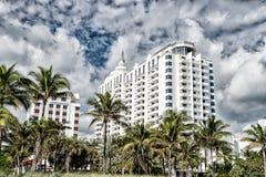 зодчество самомоднейшее Высокие здания подъема с зелеными пальмами Стоковая Фотография