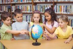 Зрачки смотря глобус в библиотеке стоковые фото