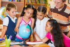 Зрачки смотря глобус с их учителем стоковые фото