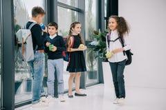 Зрачки стоя в прихожей школы и имея обед стоковые изображения rf
