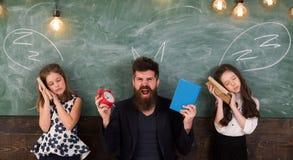 Зрачки учителя и девушек в классе, доске на предпосылке Дети и учитель с вычерченным рожками мела стоковое фото