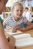 Зрачок начальной школы работая на столе в классе Стоковая Фотография