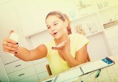 Зрачок школы девушки принимая автопортрет на smartphone пока исследование Стоковое Фото