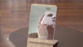 Зрелая женщина в лицевой маске для стороны Косметическая забота кожи процедуры Концентрация эмоции выбора Забота кожи концепции видеоматериал