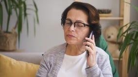 Зрелая женщина в стеклах при коричневые волосы сидя на софе сток-видео