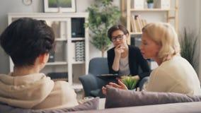 Зрелая женщина говоря с сын-подростком во время консультации с терапевтом сток-видео