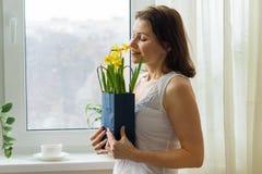 Зрелая женщина держа букет желтых цветков весны, наслаждается цветками Стоковое Изображение RF