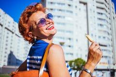 Зрелая женщина есть мороженое на солнечный день стоковое фото rf