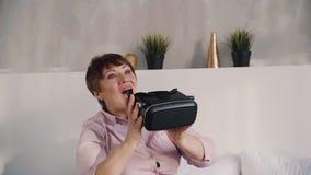 Зрелая женщина извлекает шлем виртуальной реальности из головы видеоматериал