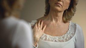 Зрелая женщина касаясь ее сморщенной шеи перед зеркалом, процессом старения видеоматериал