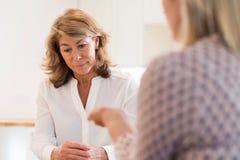 Зрелая женщина обсуждая проблемы с советником Стоковое Фото