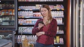Зрелая женщина покупая качественные продучты в гипермаркете акции видеоматериалы