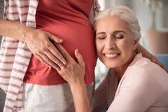 Зрелая женщина при славный обнажённый состав кладя ее ухо около беременного tummy Стоковые Фото