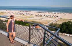 Зрелая женщина родившийся во время демографического взрыва представляя на пляже балкона обозревая и стоковая фотография rf