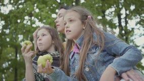Зрелая женщина сидя под деревьями в парке с 2 милыми внучками Девушки есть яблоки смотря прочь t видеоматериал