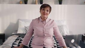 Зрелая женщина смотря камеру и сидя на кровати видеоматериал