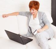 Зрелая женщина смотря компьтер-книжку Стоковое Фото