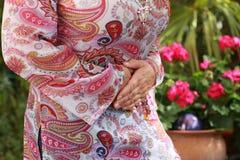 Зрелая женщина со строгой болью в животе летом стоковая фотография