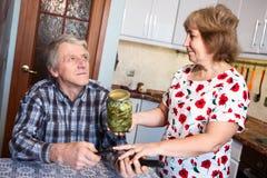 Зрелая женщина спрашивая, что занятый супруг раскрыл стеклянный опарник с marinated огурцами пока он смотря ТВ стоковые изображения rf