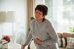 Зрелая женщина страдая от боли в животе Стоковые Фото