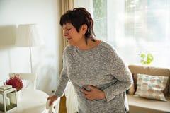 Зрелая женщина страдая от боли в животе Стоковые Фотографии RF