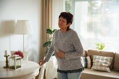 Зрелая женщина страдая от боли в животе Стоковое Изображение