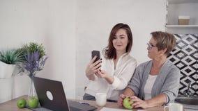 Зрелая и средн-достигшая возраста женщина говоря на клетчатом видео-звонке на акции видеоматериалы
