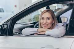 Зрелая коммерсантка выбирая новый автомобиль на дилерских полномочиях стоковое изображение rf
