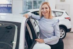 Зрелая коммерсантка выбирая новый автомобиль на дилерских полномочиях стоковые изображения rf