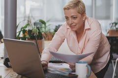 Зрелая коммерсантка работая на офисе стоковое фото rf