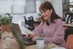Зрелая коммерсантка работая на офисе стоковая фотография